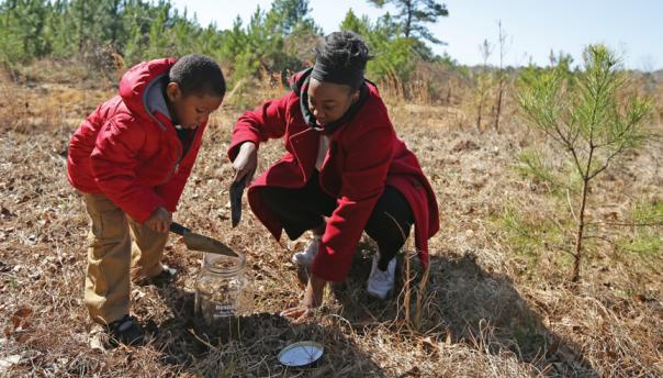 Mother and child collect soil from site of a lynching in Alabama