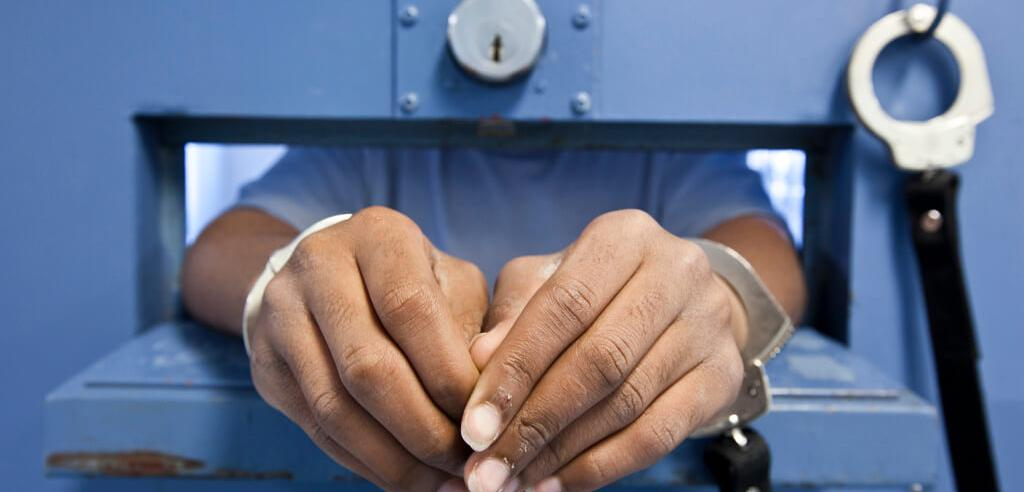 Hands of juvenile through slot in cell door