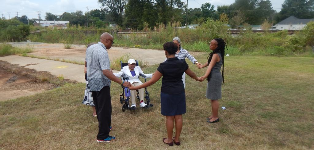 Mamie Kirkland, in wheelchair, holds hands in prayer with family and EJI staff at site of lynching