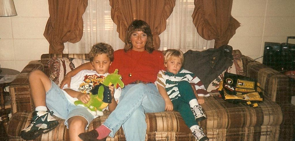 Marsha Colbey sits between her two sons on the couch in her home in 1997