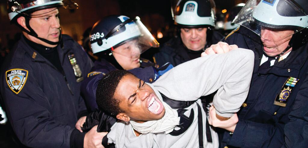 Four white New York City police officers arrest demonstrator during march for 16-year-old Kimani Gray, shot to death by police
