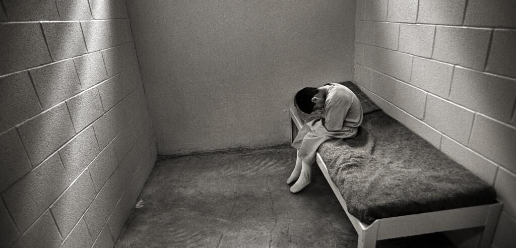 Small child alone in cell sitting on cot with head down