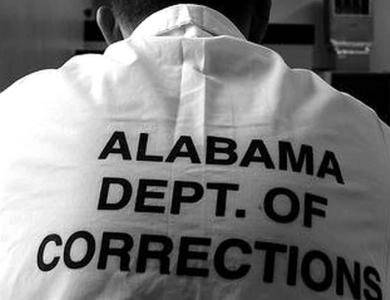 "Back of man's shirt stamped with ""Alabama Dept. Of Corrections"" in bold letters"