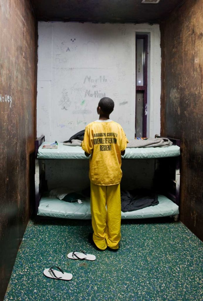 Young black boy in yellow jumpsuit in detention cell