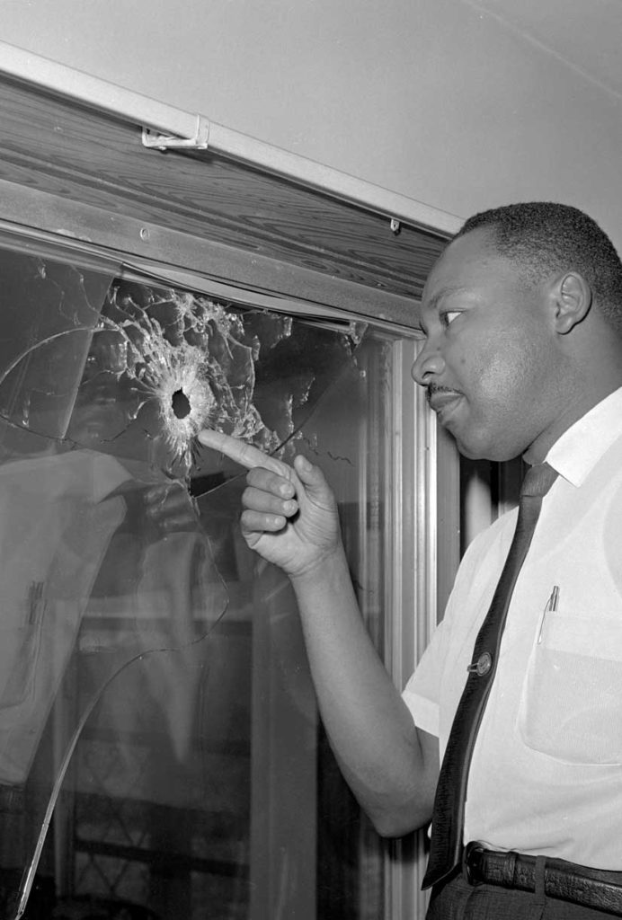 Dr. King inspects a bullet hole in the glass door of his rented cottage in St. Augustine, Florida, on June 5, 1964