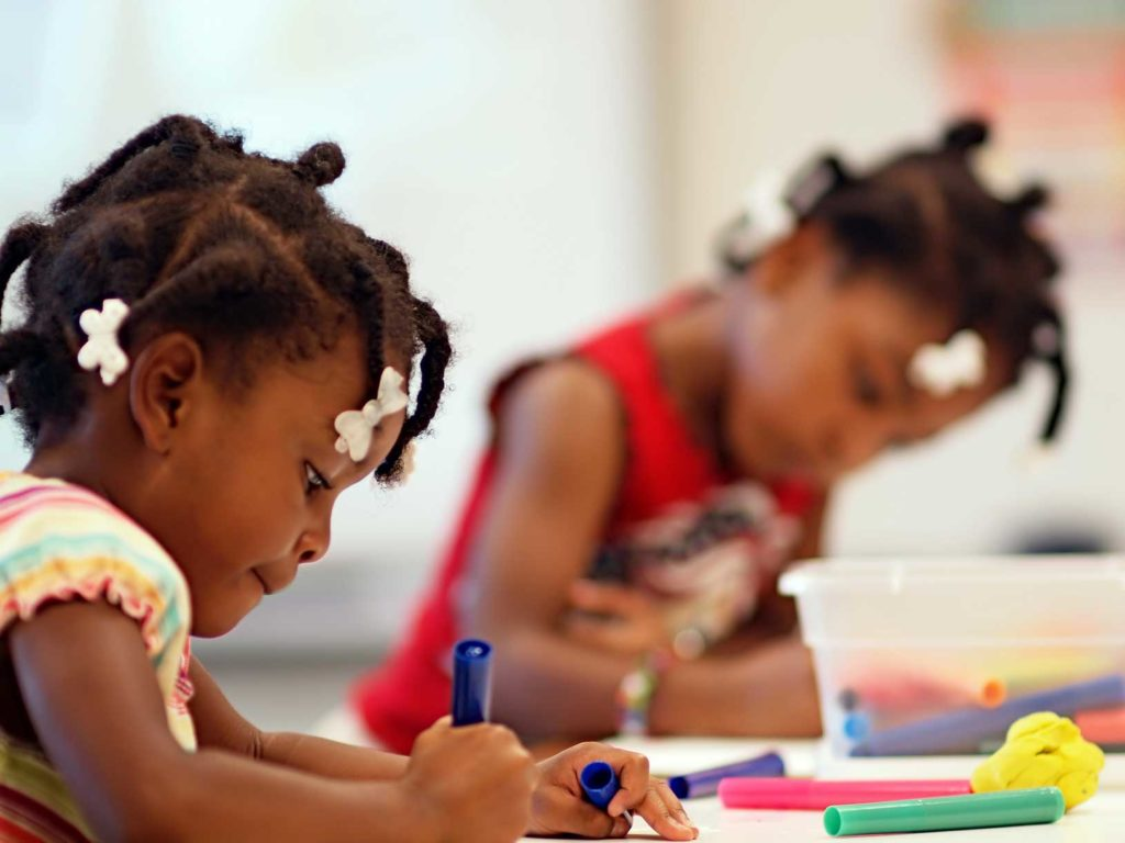 Two young African American girls coloring in school