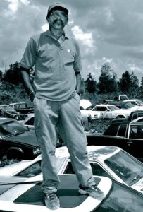 Walter McMillian standing on a car in his junkyard after his release from death row.